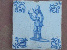 Antique tile with a pipe smoker
