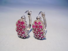 Earrings with rubies and white topaz entourage totalling 3.40 ct.
