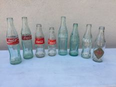 8 empty bottles of coca cola, from various countries