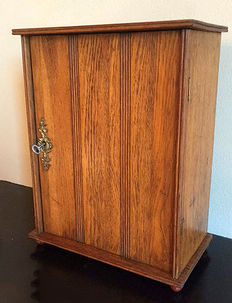 An oak Art Deco cabinet with three compartments, suspension point and key, ca. 1930