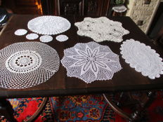 Lot of nine white round crochet doilies.