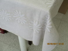 Beige linen table cloth linen with woven flowers.