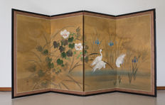 A signed four-part folding screen (byōbu). Decorated with hand-painted blue irises, white hibiscus and white herons against a background of  gold-leaf flakes - Japan - around 1950 (Showa period).