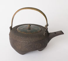 A special, three-legged cast iron sake kettle (chōshi). With a cloisonné lid and decorated with chrysanthemum and paulownia flowers in a light relief - Japan - 19th century (Meiji period)
