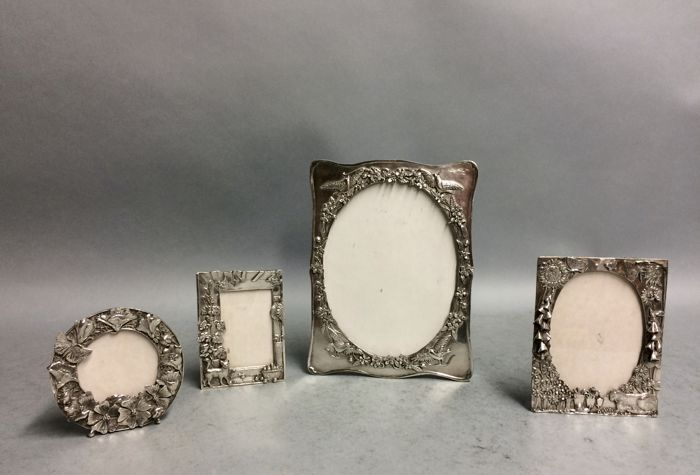 Four silver plated photo frames with floral decoration and inscription, England, ca 1930
