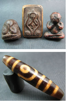 A 2 eye dzi bead and a collection of 3 Phra Pidta sacred powder amulets - Thailand and Himalayan regions - mid to third quarter of the 20th century.
