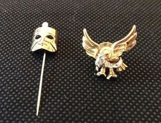 Two 18 ct yellow and white gold brooches, depicting a flying eagle and a mask.