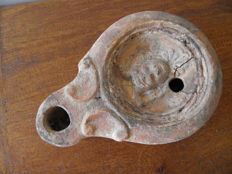 Roman oil lamp decorated with a horned head of a god - 95 mm