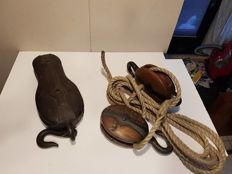 Three antique maritime pulleys with rope