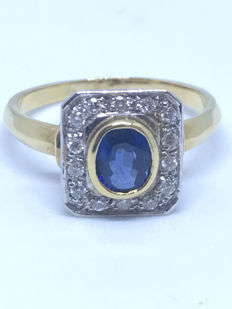 pretty gold ring adorned with a sapphire and diamond entourage