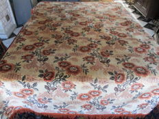 Retro tablecloth of velour with flower print, bordered around with fringes.
