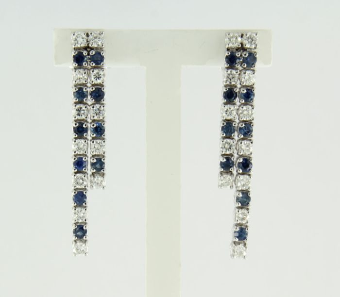 18 kt white gold dangle earrings set with 20 sapphires and 24 brilliant cut diamonds of approx. 0.77 carat in total, measurements are 30 mm x 4.6 mm wide.