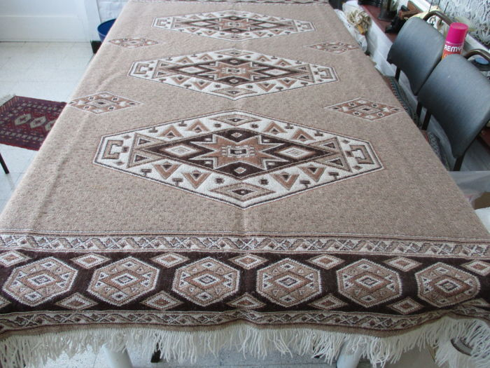 Heavy wool table carpet bordered with woollen tassels.