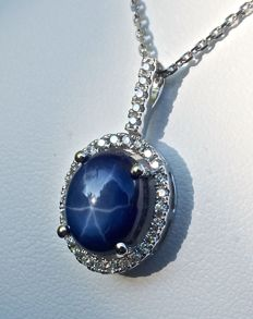 Superb certified 5 ct oval cabochon star Sapphire, in a pendant on an 18 kt white gold necklace, with hinged bale and brilliant cut diamond entourage of 0.26 ct in total