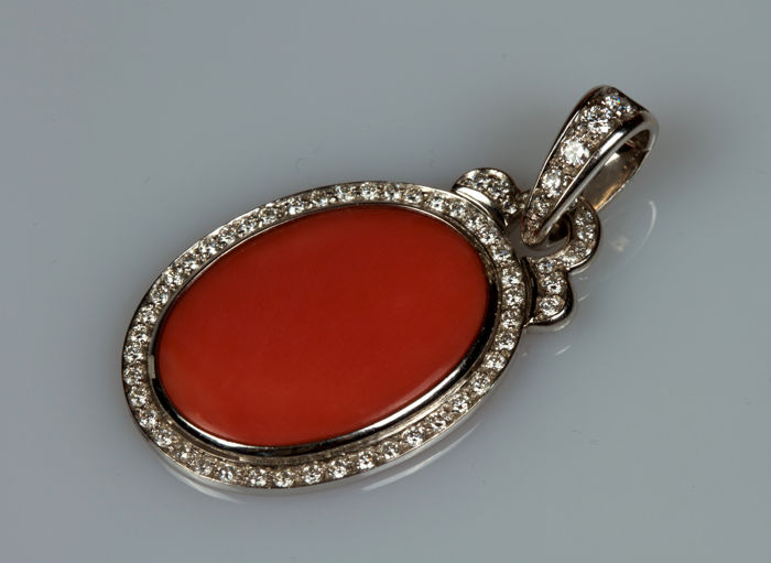 White gold pendant with oval-shaped coral surrounded by diamonds. Dimensions: 4 x 2 cm