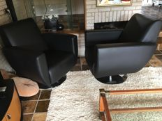 Manufacturer unknown - two modern black leather armchairs on metal swivel foot.