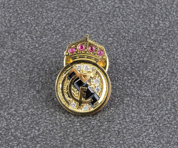 Real Madrid crest of 18 kt (.750) yellow gold with 8 inlaid diamonds of 0.20 ct in total, 4 rubies and 4 sapphires