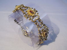 Bracelet with garnet roses in gold cartouches.