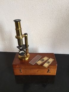 A brass microscope with glasses in a box, early 20th century