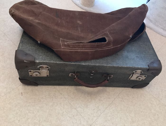 Old vintage suitcase with its protective cover in canvas, inscription on the clasps and with travel label