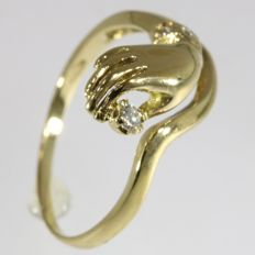 Gold hand holding diamond ring - anno 1970