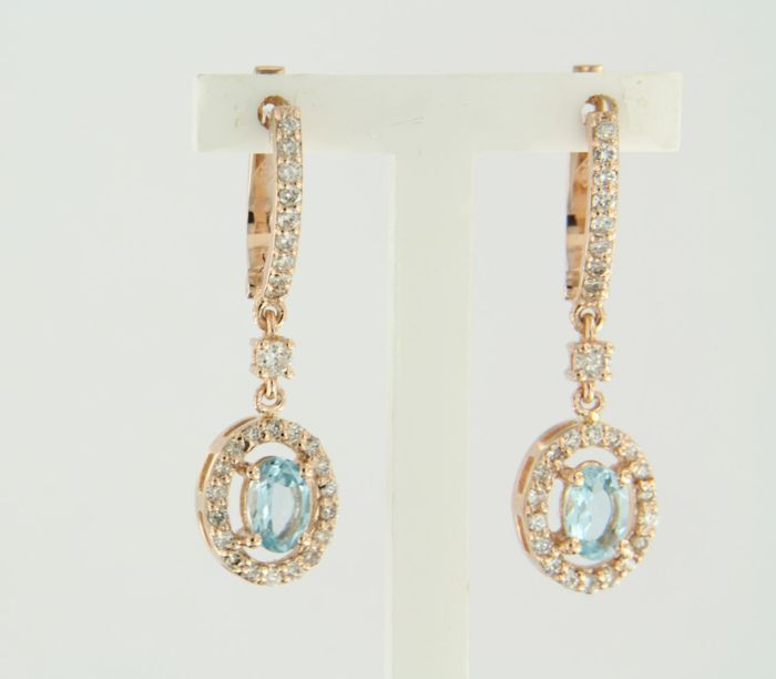 14 kt rose gold dangle earrings set with a central, oval cut blue topaz and 58 brilliant cut diamonds of approx. 0.60 ct in total *** NO RESERVE PRICE ***