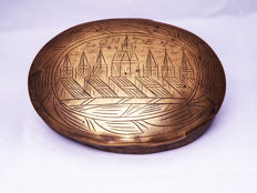 A lid of an oval yellow copper seventeenth century Dutch tobacco box with an image of London at that time.