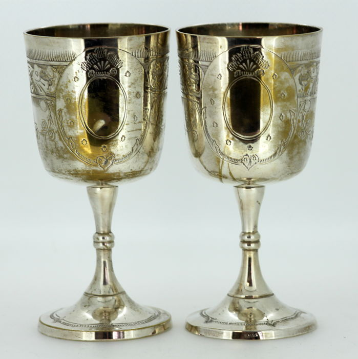 Pair of silver plate wine glasses with decorative engravings, ca.1920
