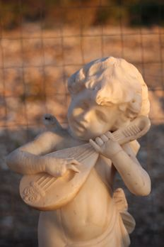 Carrara marble sculpture depicting a Cupid playing on a violin - mid-19th century