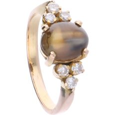 18 kt - Rose gold ring set with an oval, cabochon cut chrysoberyl with cat's eye effect and 6 brilliant cut diamonds of in total approx. 0.18 ct in a yellow gold setting - Ring size: 16.5 mm