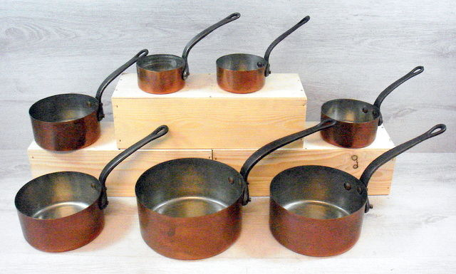 Set of 7 red-tinned copper saucepans