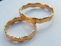 Lot of two decorated wedding rings in yellow 18 kt gold.
