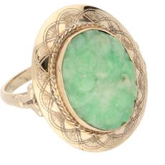 14 kt Yellow gold ring set with a cut Jadeite in an elegantly worked setting.
