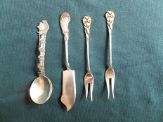 One lot of 4 silver cutlery pieces, 1 sugar spoon, 1 butter-knife and 2 pickle forks.  Netherlands 20th century.