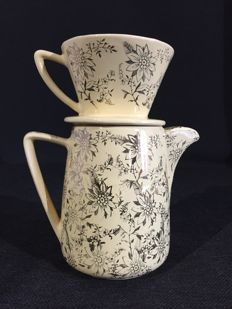 Vintage porcelain coffee pot and filter with gold -coloured and black floral patterns.