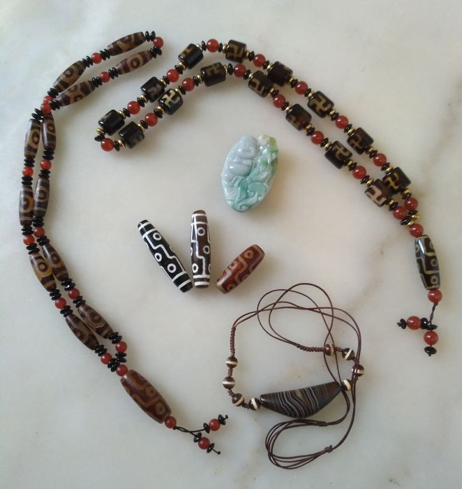 Lot of jewellery with two necklaces, a pendant, three dzi beads and a jade pendant - second half of the 20th century