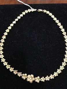 Choker in 14 kt gold in the shape of small flowers.