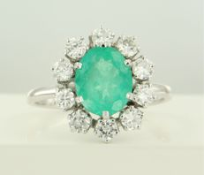 18 kt white gold rosette ring set with a central oval cut emerald and 10 brilliant cut diamonds, ring size 19 (59)