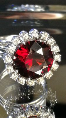Exclusive ring with beautiful pure garnet of 9.03 ct, natural diamonds 0.64 ct made of 18 kt gold.  IGE certificate.