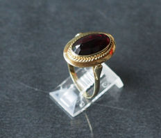 Gold ring with 1 oval faceted cut garnet.