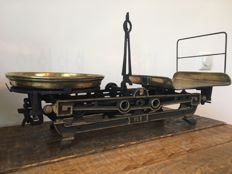 Old cast iron balance scales with brass scales.