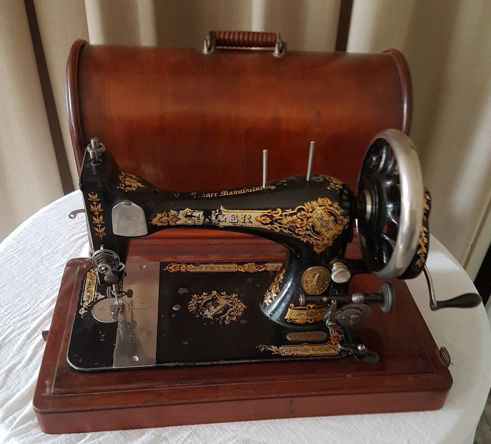 Authentic Singer hand sewing machine with wooden dust cover from 1886