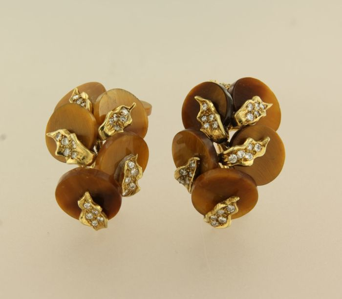 14 kt yellow gold clip-on earrings set with a tiger eye and 60 brilliant cut diamonds, approximately 0.75 ct in total