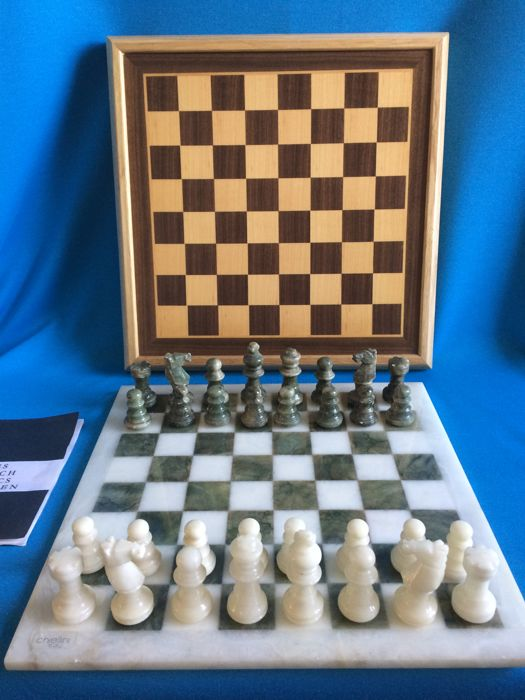 2 chess sets 1 of Onyx Chiellini and 1 of wood with game rule booklet.