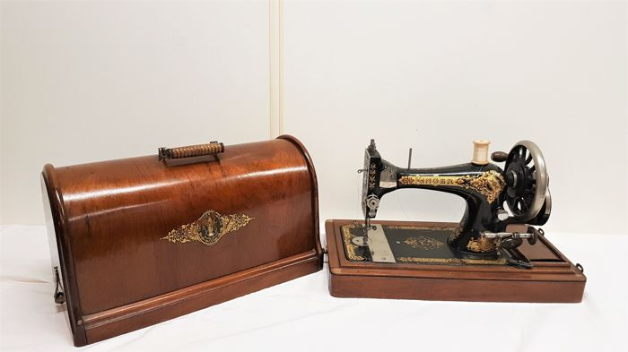 Singer sewing machine with wooden hood, ca. 1900