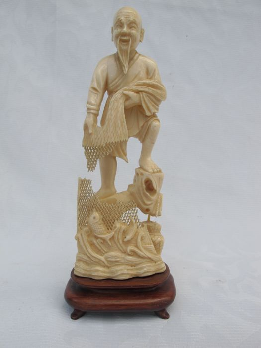 Statue of a fisherman who caught too many fish, carved from ivory, on wooden base - China - 1930