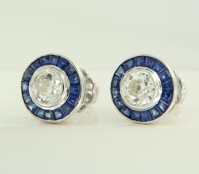 14 kt white gold ear studs set in the centre with 2 Bolshevik cut diamonds and an entourage of taper/carré cut sapphires, 32 in total, of approx. 3.50 ct in total