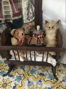 Old solid wooden crib for doll, full of antique toys