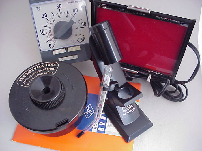 Some darkroom accessories: Enlarging paper, a focus scope, a thermometer, a timer clock, and a 35 mm developing tank (with spiral)