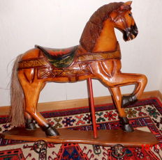 Vintage handcrafted solid wooden horse on wheels with pulling device, manufactured around 1910